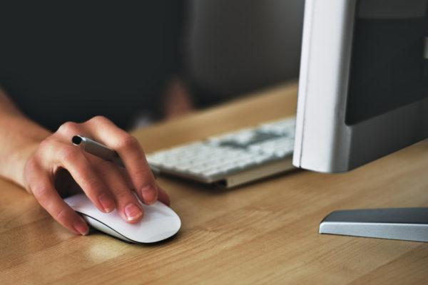 パソコンをマウスで操作する男性