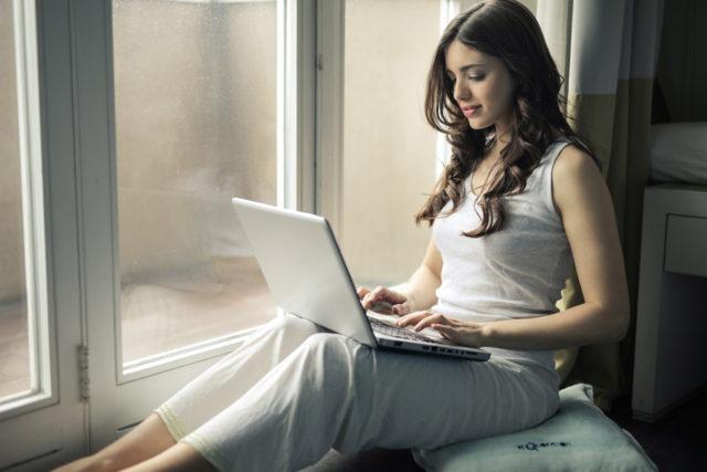 窓際でパソコンを触る女性の画像